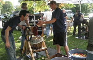 Volunteers pressing apples into cider which was donated to local food pantries